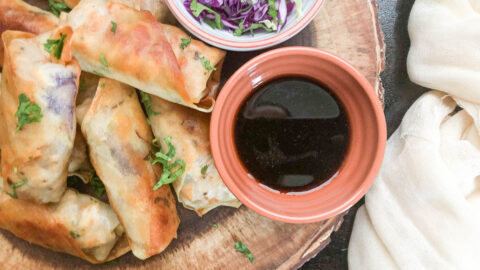 spring rolls on wooden serving try with dipping sauce