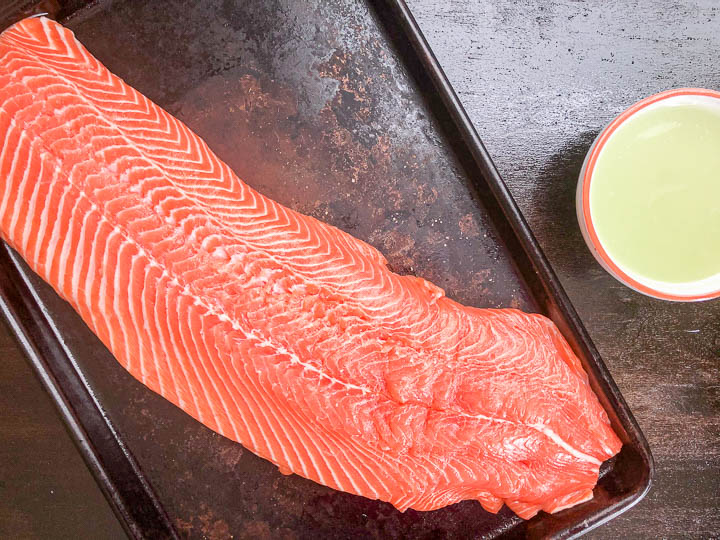 raw salmon on quarter size baking sheet with skin removed