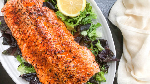 lemon garlic broiled salmon on top of bed of lettuce on white plate