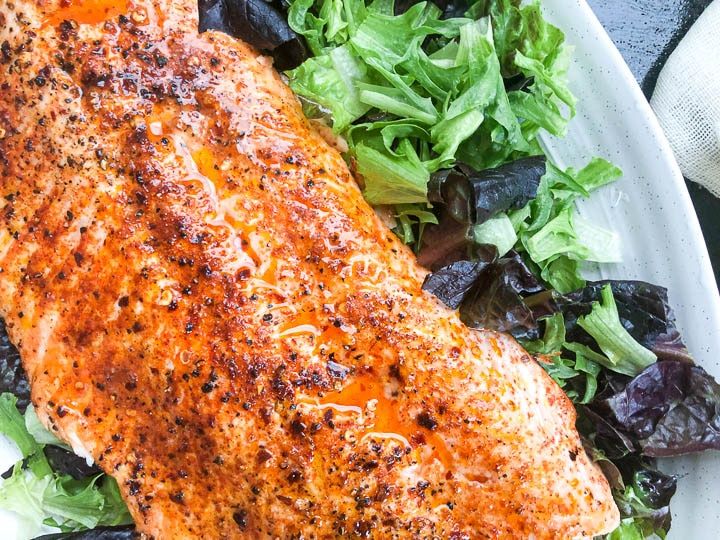 broiled salmon on top of bed of leafy lettuce