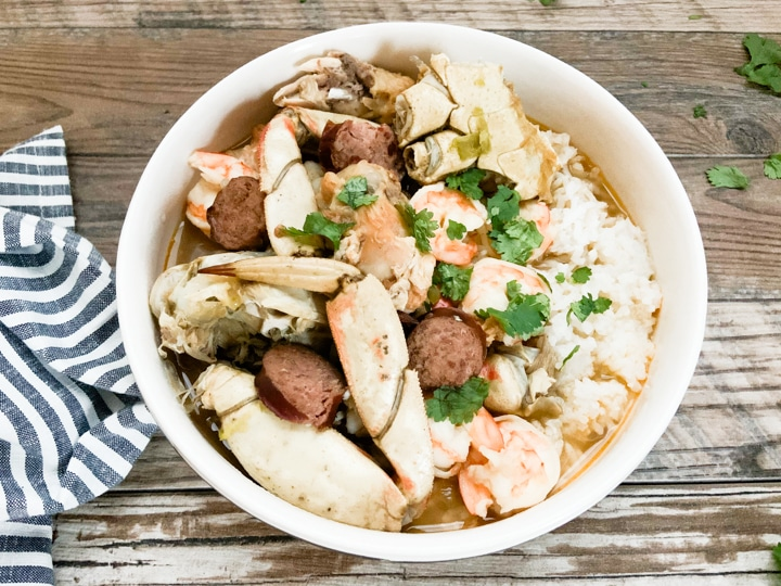 Seafood chicken gumbo served in white bowl with rice topped with parsley