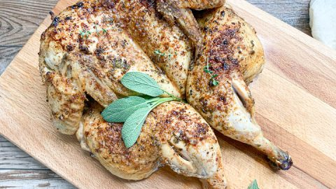 whole roasted chicken on wooden cutting board