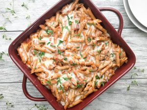 Easy Baked Ziti served in a square burgandy baking dish
