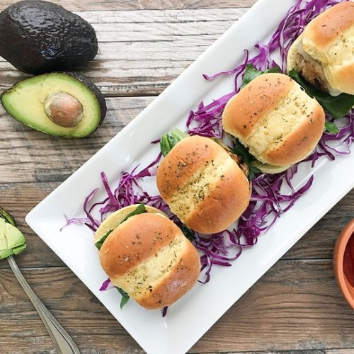 turkey sliders sandwiched between 2 Hawaiian rolls served on a white serving tray