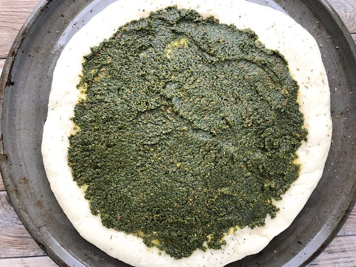 pesto sauce spread across pre-baked pizza dough