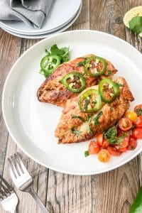 baked mediterranean chicken breast served on a white plate with roasted tomatoes