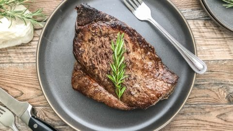 london broil that has been cooked in oven served on a bluish gray dinner plate