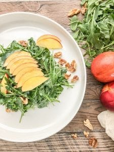 simple arugula salad with nectarines served on a while plate garnished with pecans and sliced nectarines