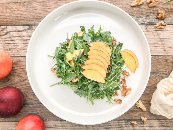 top view of simple arugula salad with nectarines and toasted walnuts