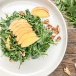 frontal view of simple arugula salad with nectarines