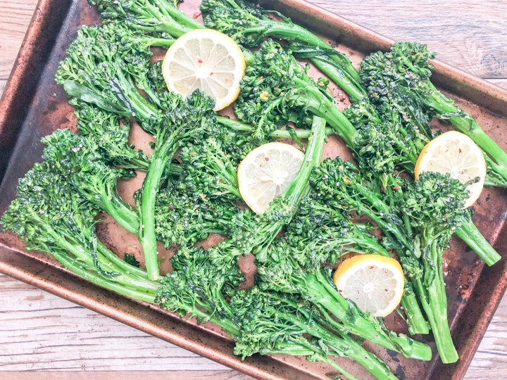 oven roasted broccolette recipe garnished with lemon and crushed red peppers