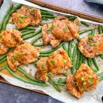baked chicken and green beans on a sheet pan topped with sliced green onions