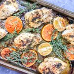 citrus herb chicken recipe in a sheet pan garnished with fresh thyme