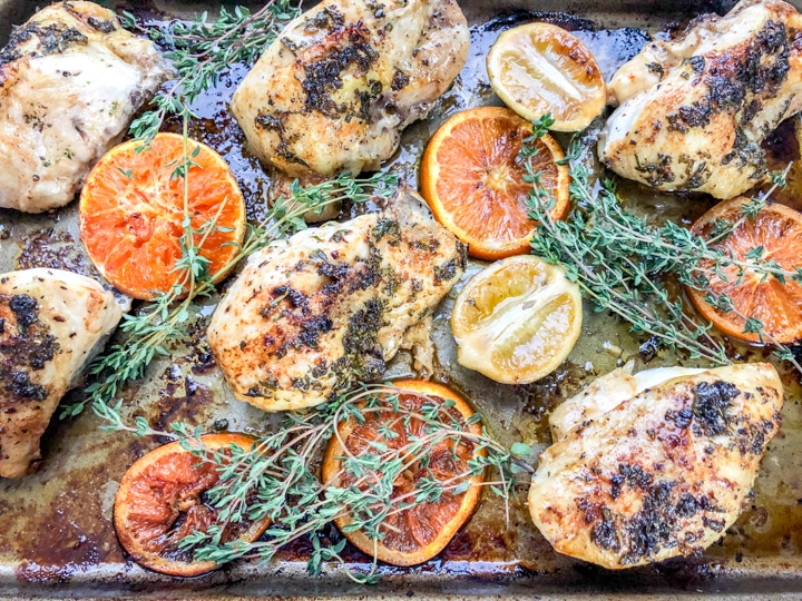citrus herb chicken recipe in sheet pan with sliced oranges ready to be served