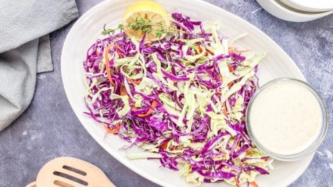healthy coleslaw recipe no mayo in a cream colored serving bowl with a side of tahini salad dressing
