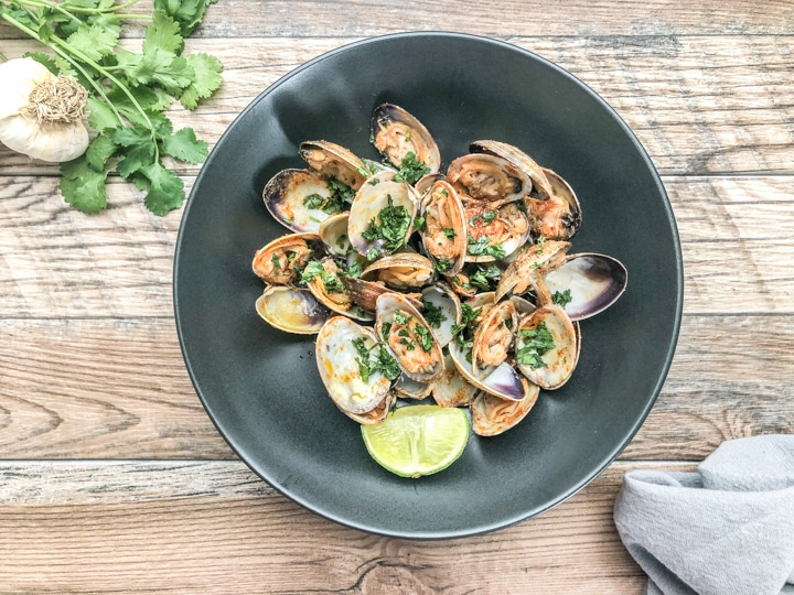 final shot of steamed clams in black bowl with a gray cloth dinner napkin