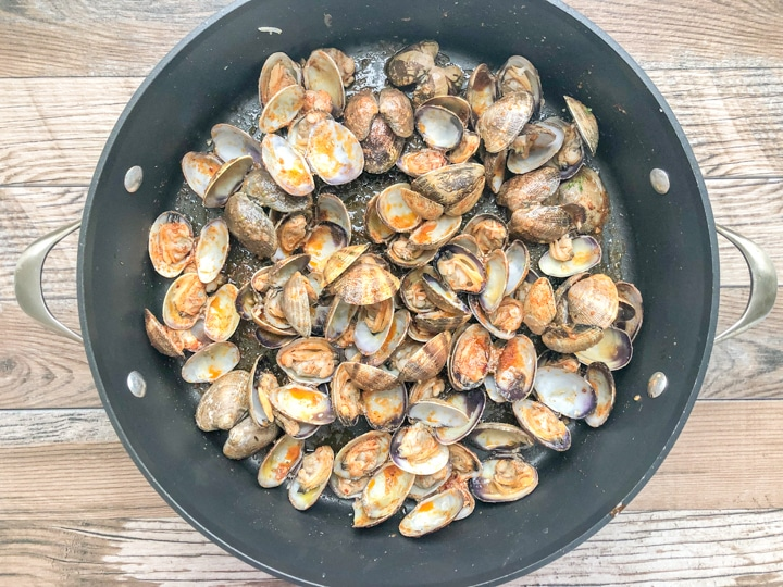 steamed clams in sauce pan drizzled with Cajun marinade