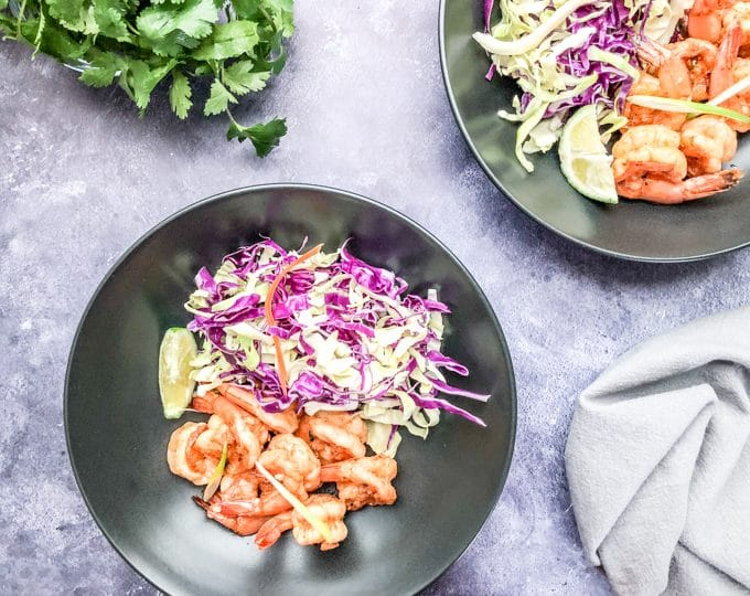 shrimp bowl recipe served in a black bowl with green and purple cabbage and tahini dressing