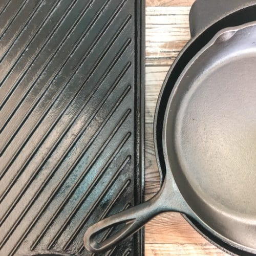 seasoned cast iron grill and skillet laying on a backdrop