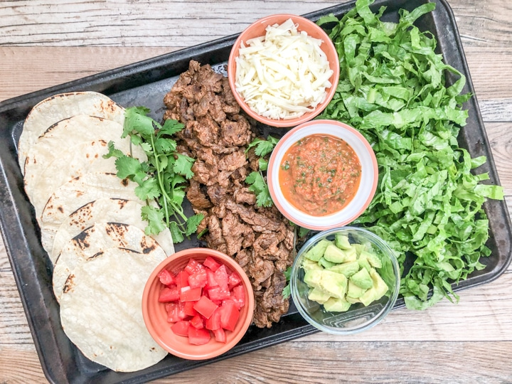 soft taco recipe with flap meat and toppings on rustic baking sheet