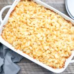 creamy baked mac and cheese in a white casserole dish with plates on side