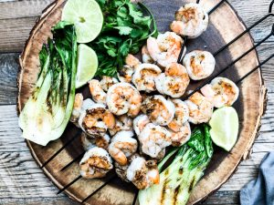 grilled shrimp skewers on wooden serving platter with grilled bok choy
