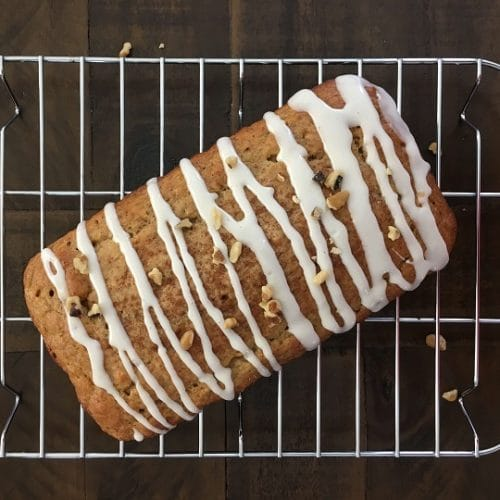 healthy banana bread drizzled with vanilla glaze on cooling rack