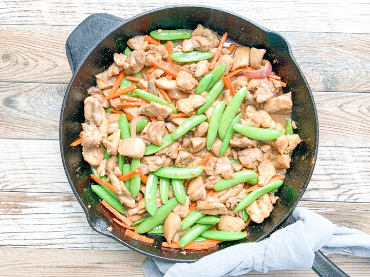 chicken stir fry in cast iron skillet with gray napkin around handle of skillet