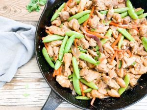 healthy chicken stir fry in black cast iron skillet