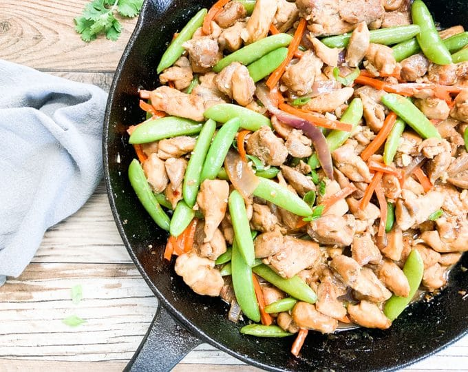 healthy chicken stir fry in black cast iron skillet