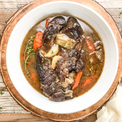 dutch oven beef stew in white bowl garnished with fresh thyme