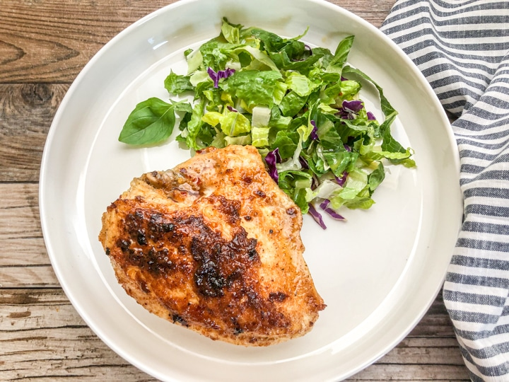 seared chicken breast on white plate with fresh green salad