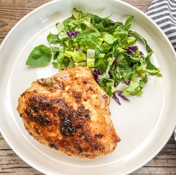 juicy chicken breast cooked in cast iron skillet served on white plate with salad