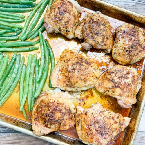 close-up of chicken and green beans in baking sheet in pan juices