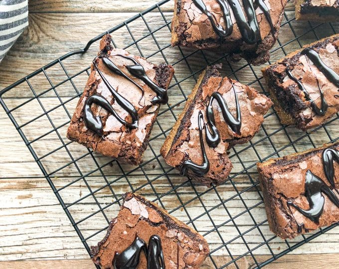 brownie cookie bars on cooling rack drizzled with fudge