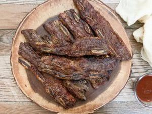grilled flanken ribs on a round wooden serving dish next to a beige napkin