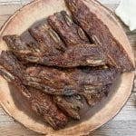 grilled flanken ribs served on a circular wooden serving dish next to a beige napkin