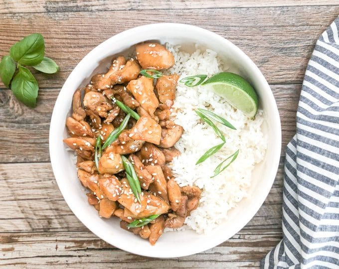 sesame chicken served with white rice in white bowl