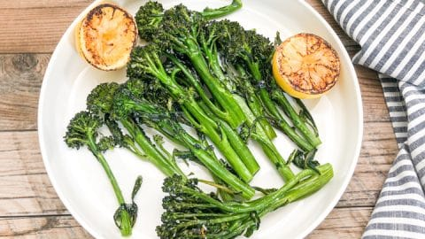 roasted broccolini on white serving plate with grilled half lemons