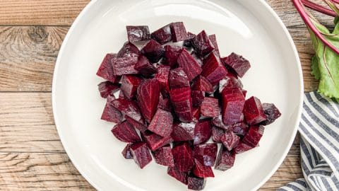 roasted beets cut into cubes on white serving plate next to striped napkin