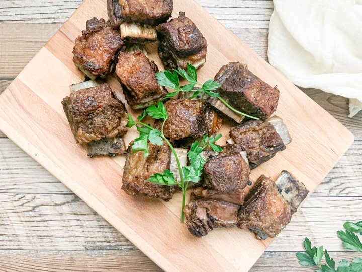 baked short ribs garnished with parsley on wooden cutting board