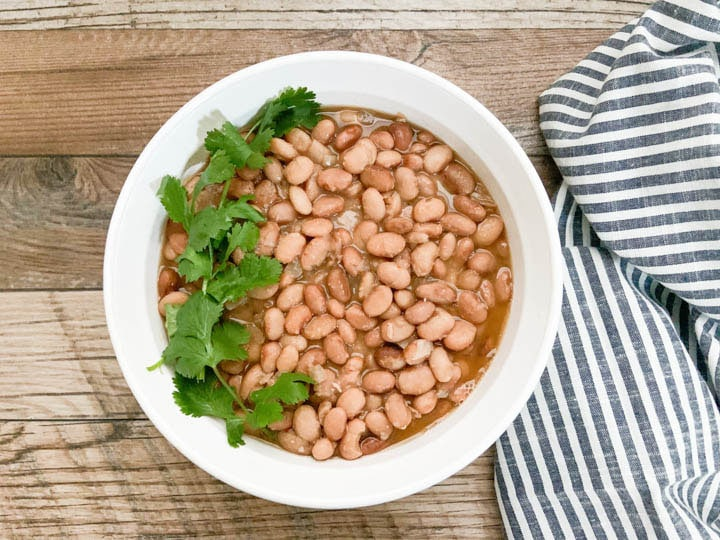 pinto beans served in white bowl with gray striped napkin