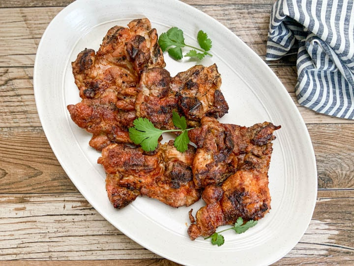 grilled chicken thighs served on oval white platter garnished with cilantro leaves