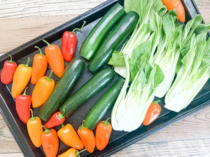 fresh sweet mini peppers, zucchini and bok choy on baking sheet