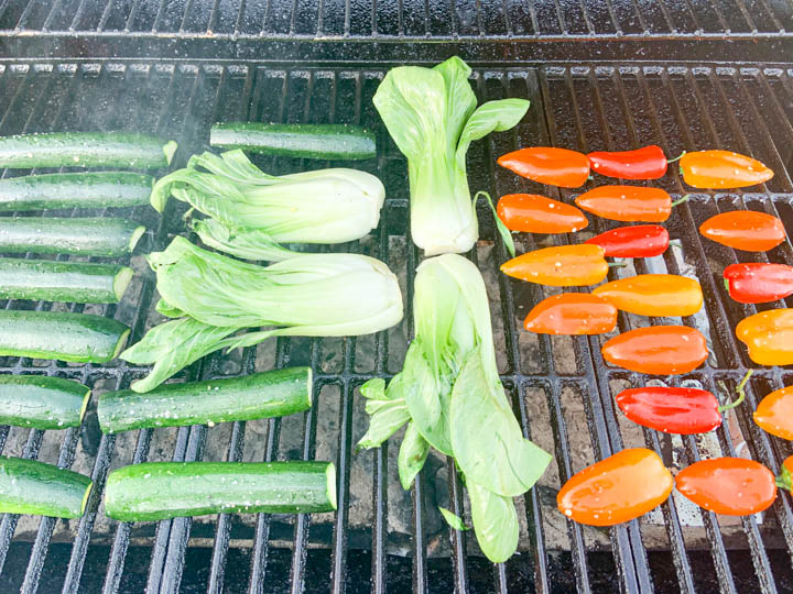 peppers, bok choy, zucchini placed on charcoal grill