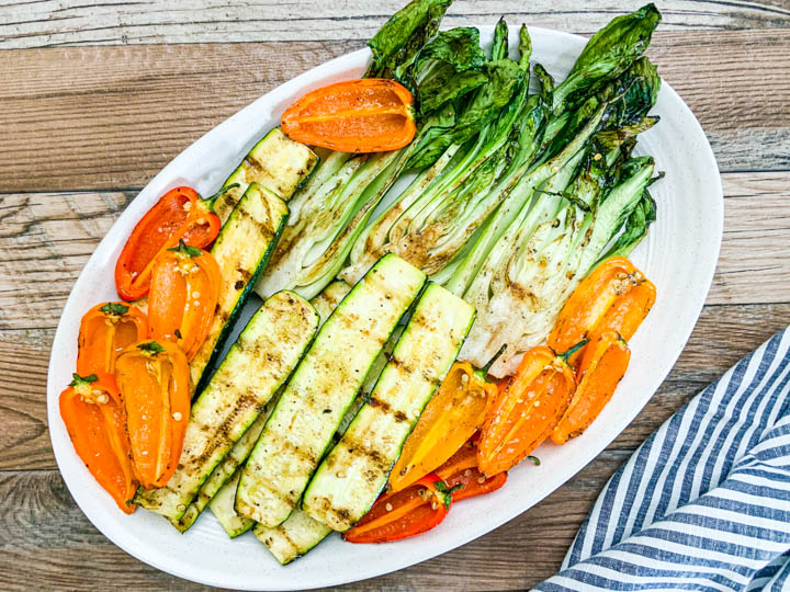 grilled sweet mini peppers, zucchini, and bok choy served on white platter