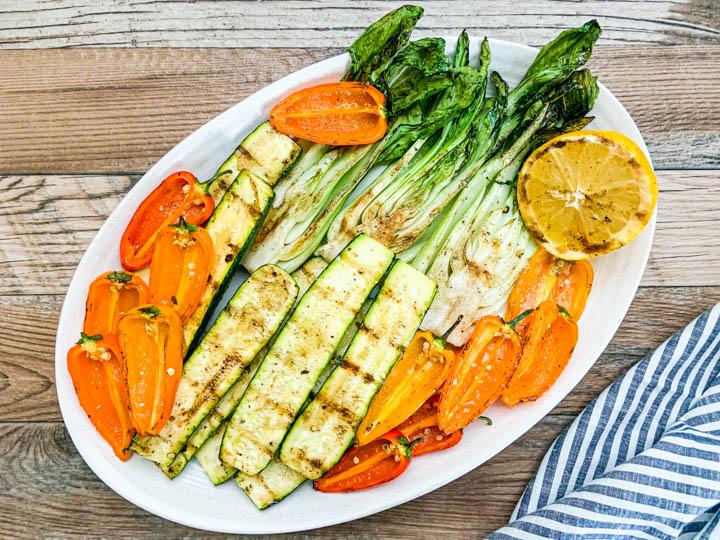 platter of grilled vegetables with slice of grilled lemon