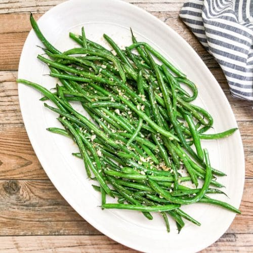 green beans served on a white platter topped with toasted panko crumbs