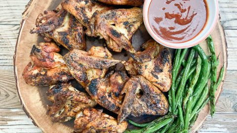 grilled chicken wings on round serving tray with grilled green beans