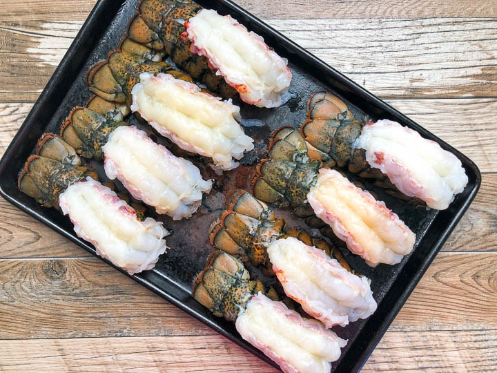 raw lobster tails on baking sheet